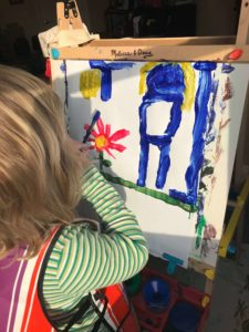 Child painting on art easel.