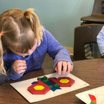 Child using pattern blocks and pattern card.